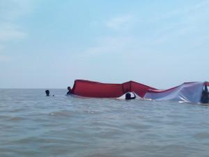 Kencangnya angin dan adanya gelombang membuat pasukan pengibar bendera kesulitan membentang sang saka merah putih di Pantai Amal