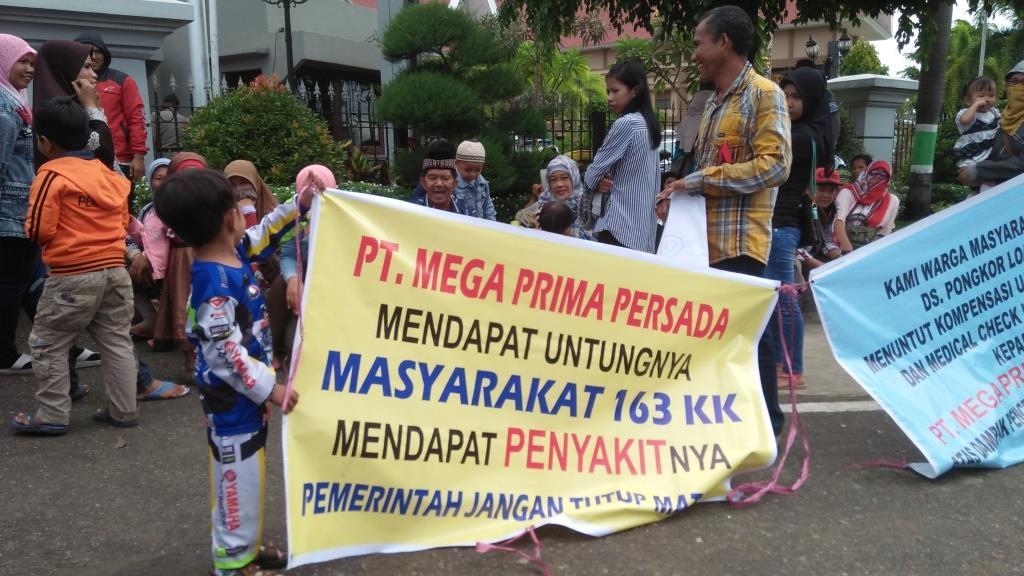 Seorang anak ikut membentangkan spandu bersama orangtuanya terkait tuntutan kepada PT. MPP di depan Kantor Gubernur Kaltim.