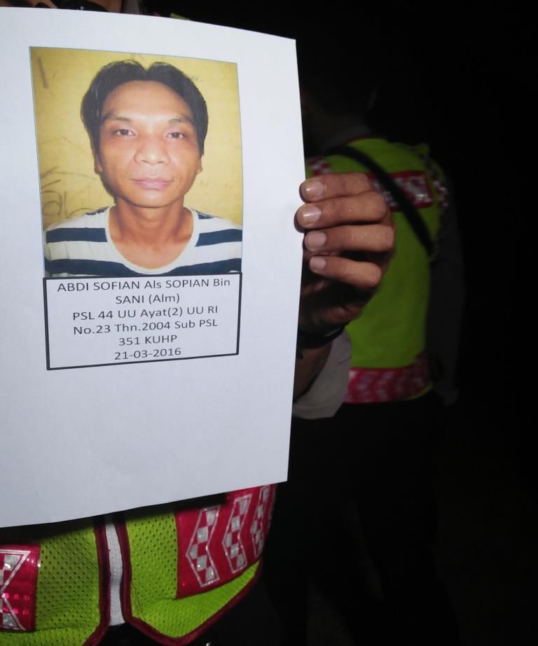Petugas kepolisian kala menunjukkan foto Abdi Sofian tahanan Polsekta Samar Ulu Samarinda yang masih dalam pengejaran.