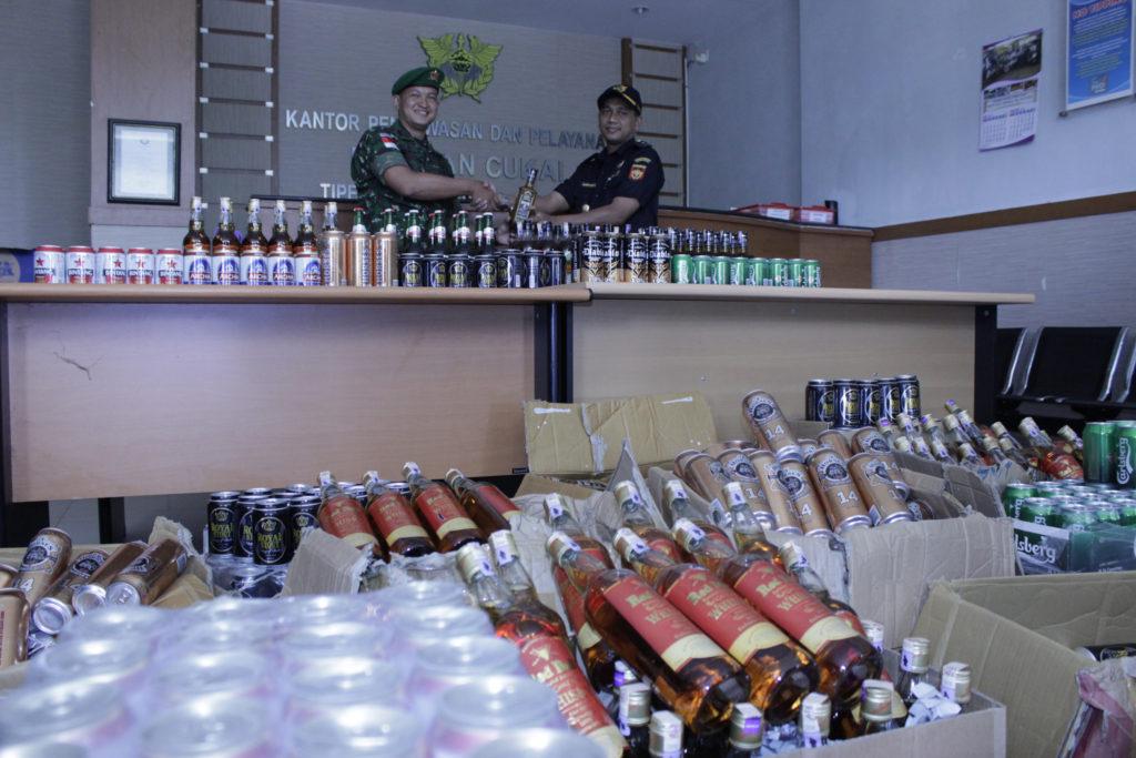 Komandan Satgas Pamtas Yonif 614/Raja Pandhita, Letkol Inf Rudi Setiawan (kiri) menyerahkan secara simbolis minuman keras tangkapan kepada Hariyanto, Kepala Seksi Pabean (kanan) di Kantor Bea Cukai Tipe D Kabupaten Nunukan, Kalimantan Utara, Selasa (23/8). Sebanyak 1.305 botol/kaleng miras berbagai jenis yang diserahkan tersebut diselundupkan dari Malaysia yang berhasil diamankan prajurit Satgas Pamtas Yonif 614/RP selama Juni-Juli 2016.